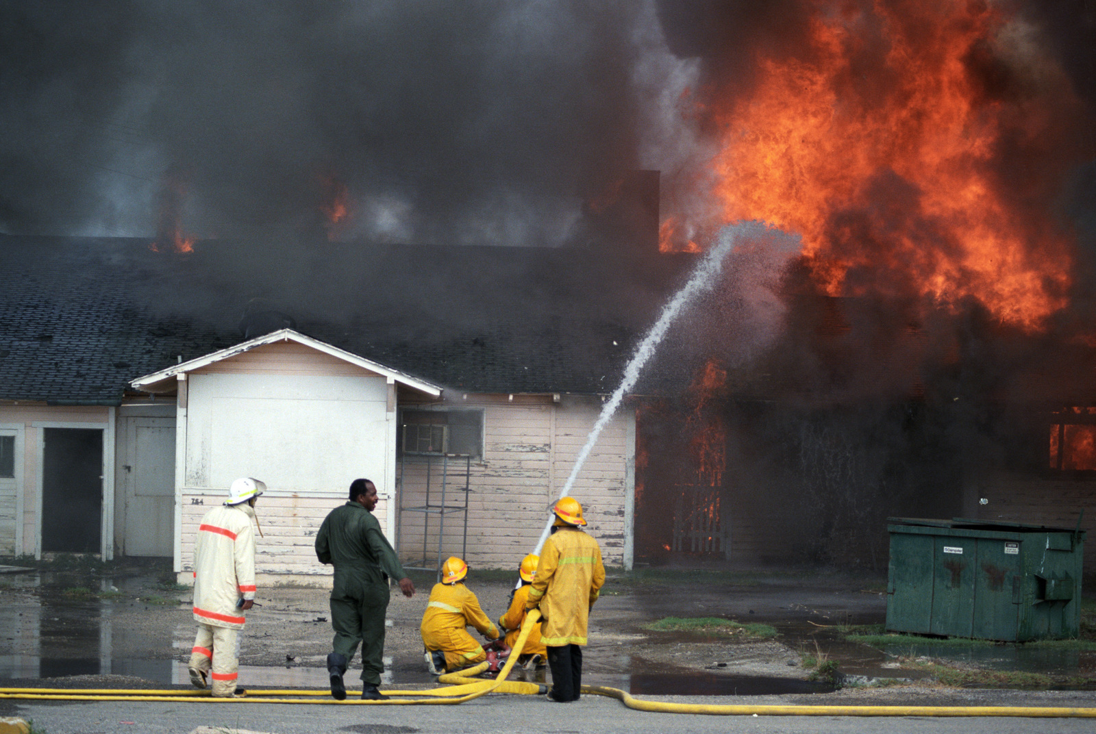 Firefighters spray water on the recreation services building after it was intentionally set ablaze during a firefighting training exercise