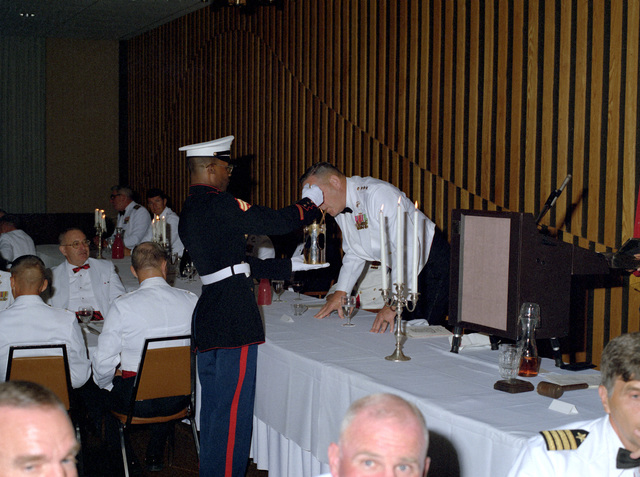 LGEN David M. Twomey, commanding general, Marine Corps Development and Education Command, lights a cigar from the smoking lamp during mess night at The Basic School