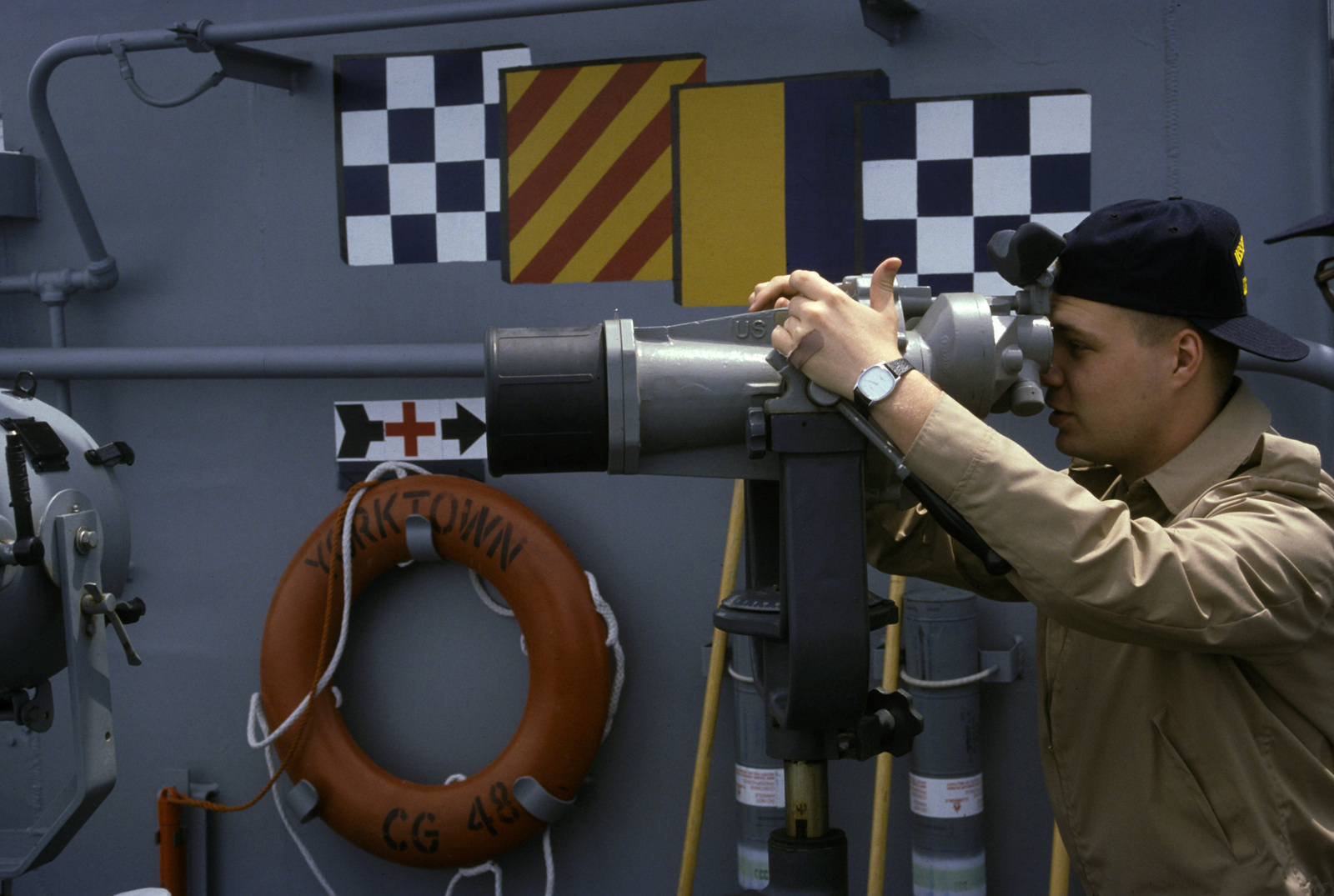 A crewman looks through a pair of high powered binoculars while standing watch aboard the guided missile cruiser USS YORKTOWN (CG 48)