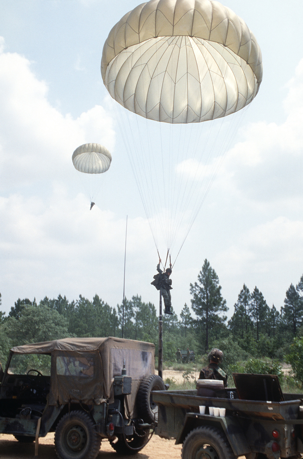 An airman decends to the ground after parachuting from a C-130 Hercules aircraft during VOLANT RODEO '86, an annual, multi-national tactical airlift competition