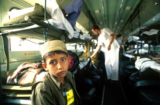 An Afghanistani child sits on the hospital bus filled with his country men on stretcher during a stop in Germany before continuing on to the United States for further treatment of their war inflicted injuries. Afghanistani refugees were treated under the auspices of the McCullen amendment, which allows DoD to make available non-combative goods for humanitarian projects
