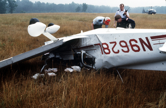 Members of the 1ST Helicopter Squadron assist COL Edwin L. Harvey, Headquarters, Tactical Air Command, as he salvages his belongings following the crash of his Grumman AA-1B aircraft near Andrews Air Force Base. Harvey was piloting the plane at the time of the accident and sustained minor injuries