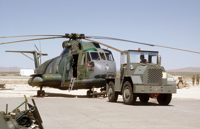 A HH-3E Jolly Green Giant helicopter is hooked to a flight line tow tractor during Exercise PATRIOT COYOTE