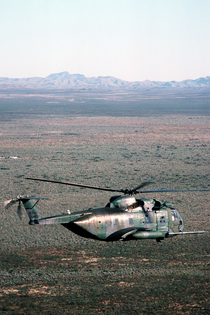 An air-to-air right side view of an HH-3E Jolly Green Giant helicopter during Exercise Patriot Coyote