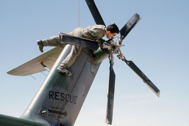 An aircraft maintenance technician checks the tail rotor of an HH-3E Jolly Green Giant helicopter during Exercise PATRIOT COYOTE
