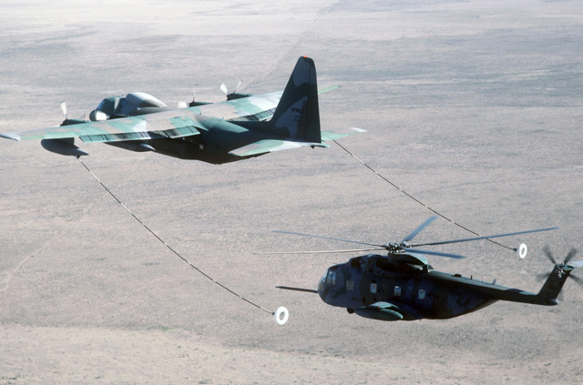 An HC-130 Hercules aircraft conducts an in-flight refueling of an HH-3E Jolly Green Giant helicopter during Exercise PATRIOT COYOTE