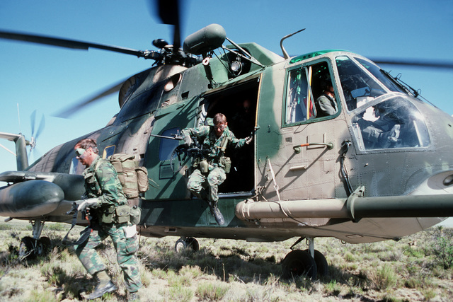 Members of a pararescue team leave an HH-3E Jolly Green Giant helicopter to begin a search and rescue mission during Exercise Patriot Coyote