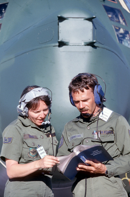 Staff Sergeant (SSGT) Susan J. Brim and Technical Sergeant (TSGT) Michael Czarnecki, 305th Aerospace Rescue and Recovery Squadron, refer to a technical manual while servicing an HC-130 Hercules aircraft during Exercise PATRIOT COYOTE