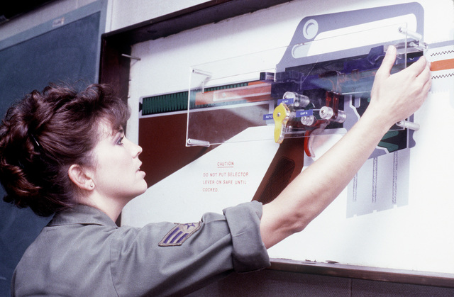 Sgt. Susan M. Cline, 833rd Security Police Squadron, combat arms training and maintenance specialist, uses a training aid to demonstrate the catch bolt movement when loading an M-16 rifle