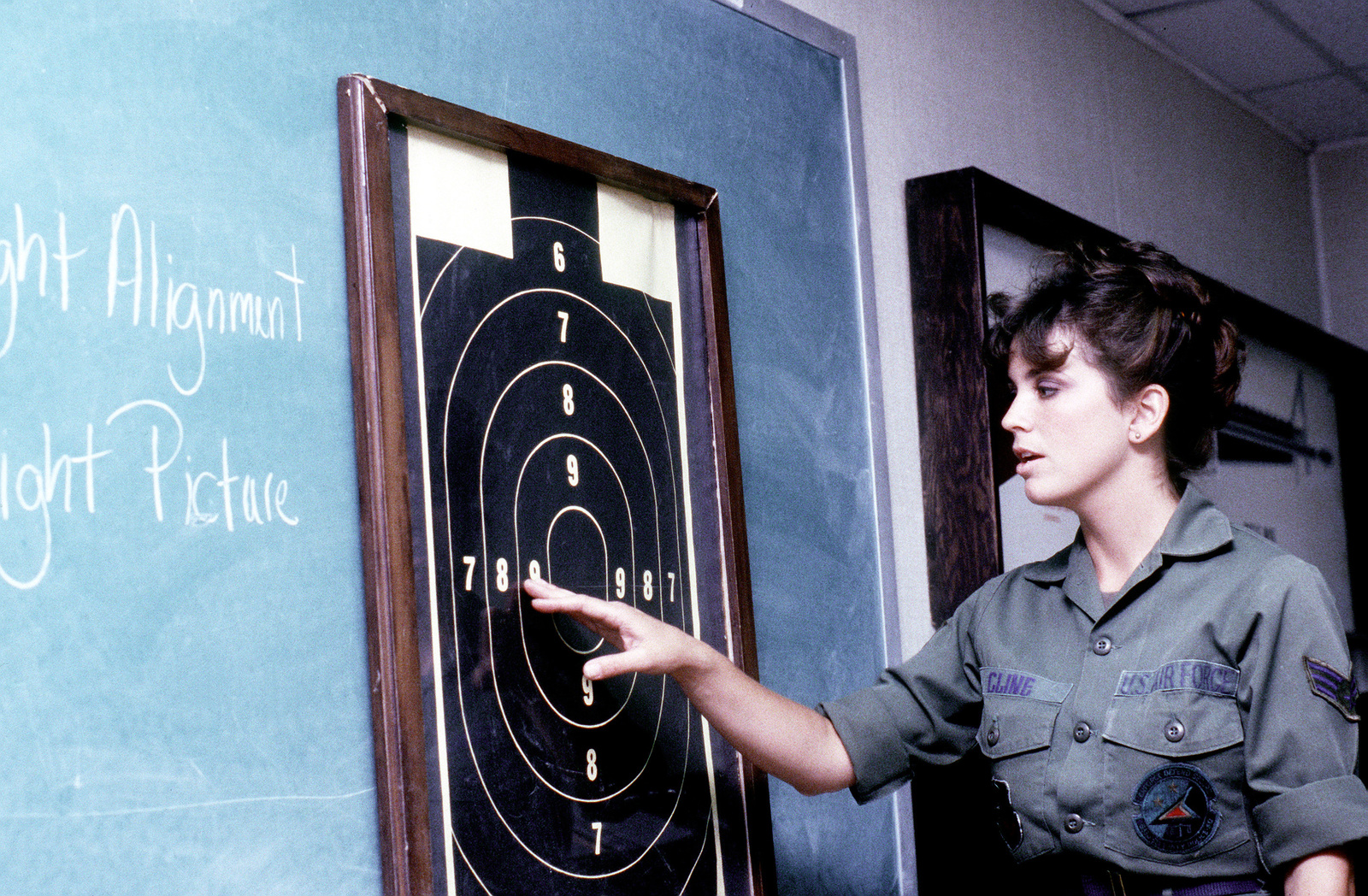 Sgt. Susan M. Cline, 833rd Security Police Squadron, combat arms training and maintenance specialist, points out score placement on a target