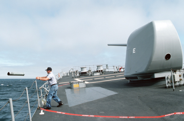 A gunner's mate pitches a spent 5-inch shell casing overboard from the deck of the destroyer USS LEFTWICH (DD 984). The ship is participating in a midshipmen's summer training cruise