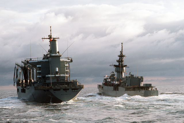 A port quarter view of the fleet oiler USS WILLAMETTE (AO 180) and the frigate USS BADGER (FF 1071) participating in an underway replenishment operation during a midshipmen's summer training cruise