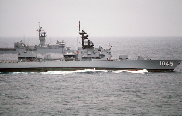 A starboard beam view of the frigates USS DAVIDSON (FF 1045) and USS SAMPLE (FF 1048), background, underway during a midshipmen's summer training cruise