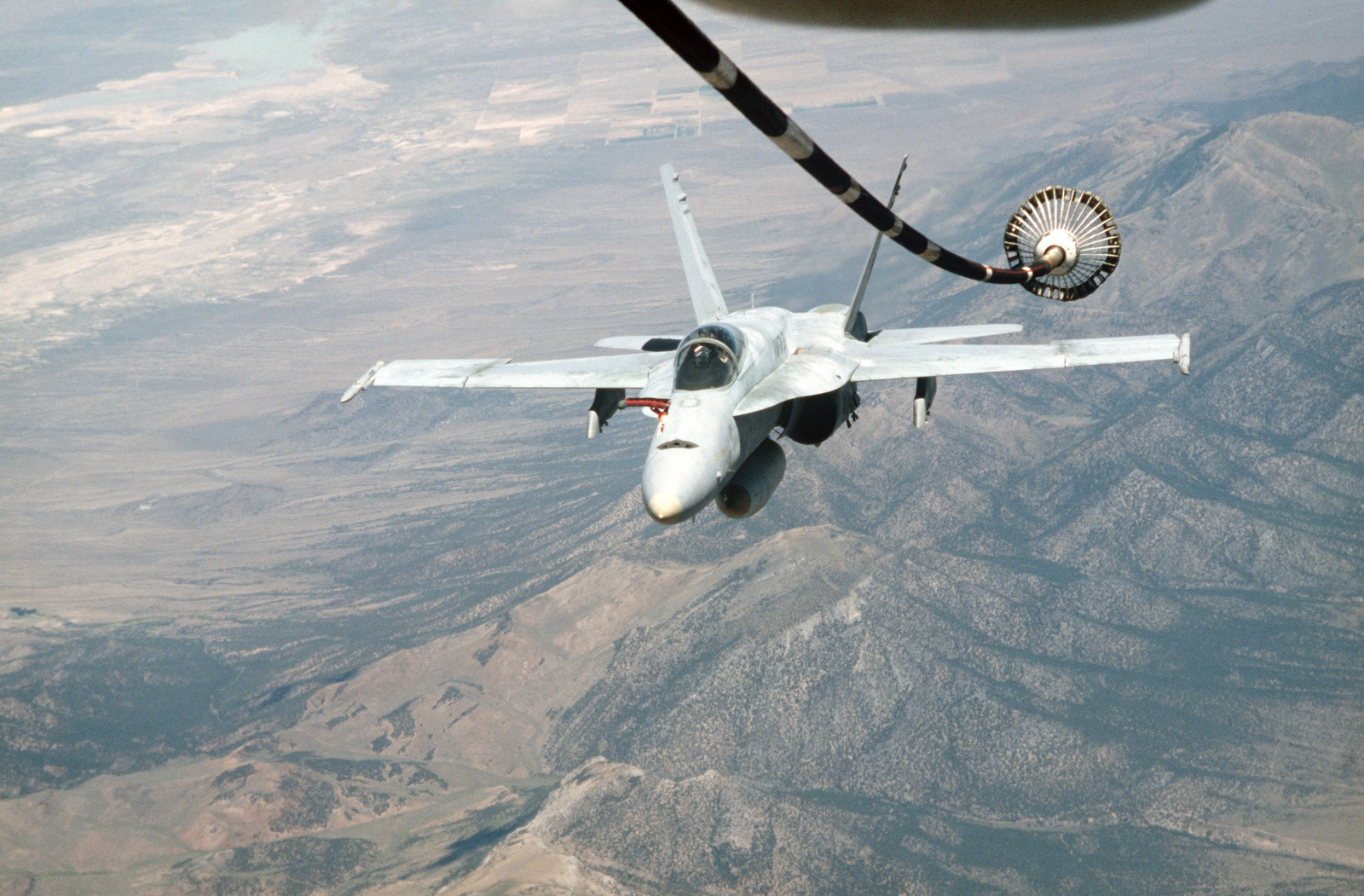 A view from the boom operator's station of a KC-10A Extender aircraft as an F/A-18A Hornet aircraft approaches for refueling during Exercise GALLANT EAGLE '86