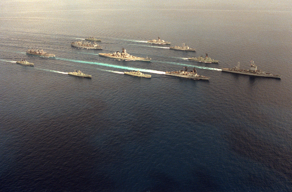 An aerial starboard bow view of the first battleship battle group to deploy to the Western Pacific since the Korean War underway with Australian ships during a training exercise. The ships are, clockwise from right: USS LONG BEACH (CGN-9), USS MERRILL (DD-976), HMAS SWAN (D-50), HMAS STUART (D-48), HMAS PARRAMATTA (D-46), USNS PASSUMPSIC (T-AO-107), USS WABASH (AOR-5), HMAS DERWENT (D-49), USS KIRK (FF-1087), USS THACH (FFG-43), HMAS HOBART (D-39) and USS NEW JERSEY (BB-62), center