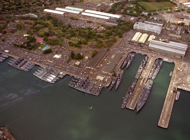 An aerial view of the harbor, looking west-southwest at Bravo piers. Japanese Maritime Self-Defense Force ships are at far left, with Canadian frigates positioned behind them. The vessels are in port to take part in exercise RimPac '86