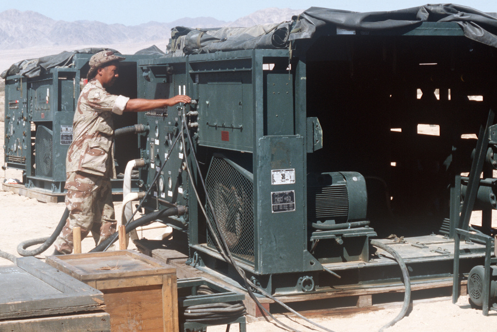 Corporal (CPL) Noli P. Aurza, hygiene equipment operator, 1ST Combat Engineering Battalion, 1ST Marine Division, checks the connectors on a reverse osmosis water purification system during Exercise GALLANT EAGLE '86