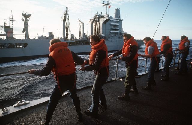 Crew members aboard the destroyer USS LEFTWICH (DD 984) haul on a line while participating in an underway replenishment operation with the fleet oiler USS WILLAMETTE (AO 180) during a midshipmen's summer training cruise