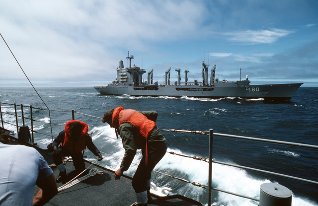 Crew members rig lines prior to an underway replenishment aboard the destroyer USS LEFTWICH (DD 984) during a midshipmen's summer training cruise. The fleet oiler USS WILLAMETTE (AO 180) is in the background