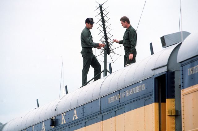 SSGT Bill Lovins, ground radio maintenance, left, and SSGT Randall Brinlee, teletype communications operator, install communications antennas on one of several converted railway cars which function as the Alaskan Air Command's Alternate Command Post. Both men are assigned to the 1930th Information Systems Squadron