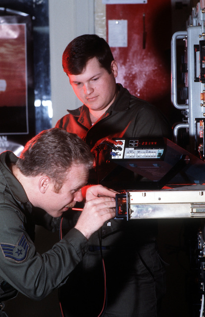 SSGT Russell Jenkins and SGT Jay Paxton, ground radio technicians with Detachment 1, 1930th Information Systems Squadron, conduct power supply checks on a GRR-24 UHF radio receiver