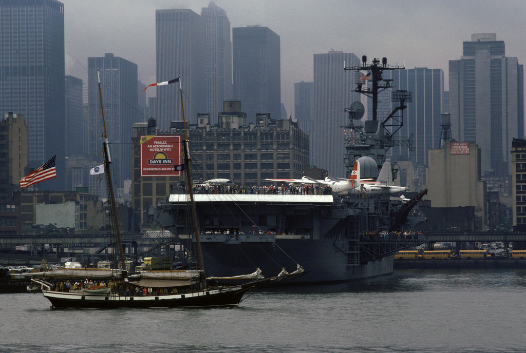 The sailing ship MYSTIC CLIPPER passes the memorial ex-USS INTREPID (CVS 11) moored at a lower Manhattan pier. The sailing ship is here for the 100th anniversary celebration of the Statue of Liberty and participation in the International Naval Review