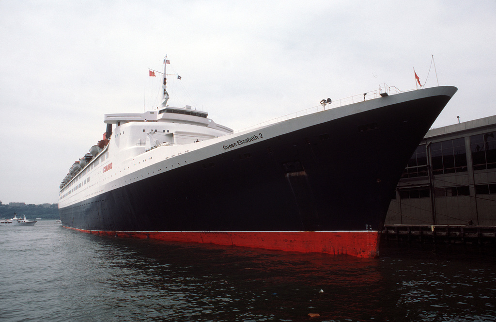 A port bow of the British passenger liner QUEEN ELIZABETH II docked at a pier during the International Naval Review
