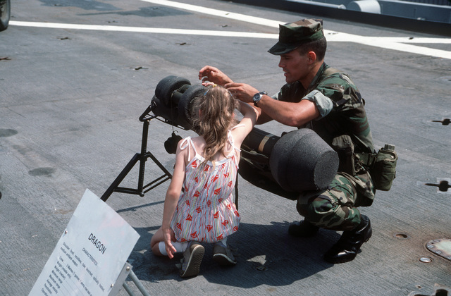 A US Marine shows an M47 Dragon anti-tank missile launcher to a child during the International Naval Review