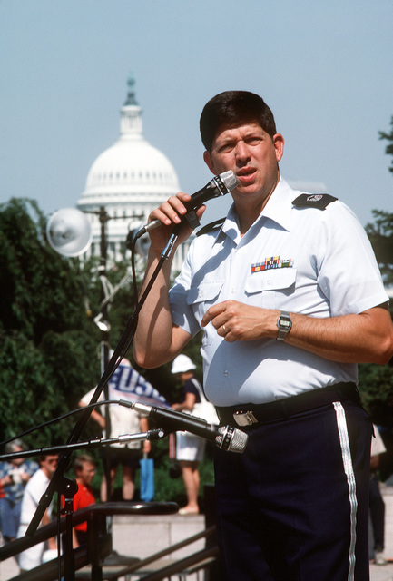 CHIEF MASTER Sgt. Dave Steinmeyer introduces the Tops in Blue, U.S. Air Force singers, during a Fourth of July show outside the National Air and Space Museum. The U.S. Capitol is in the background