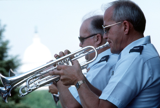 CHIEF MASTER Sgt. Larry Trautman and Senior MASTER Sgt. Jim Lay, trumpet players in the Airmen of Note, a U.S. Air Force band, perform outside the National Air and Space Museum during a Fourth of July show. The U.S. Capitol is in the background