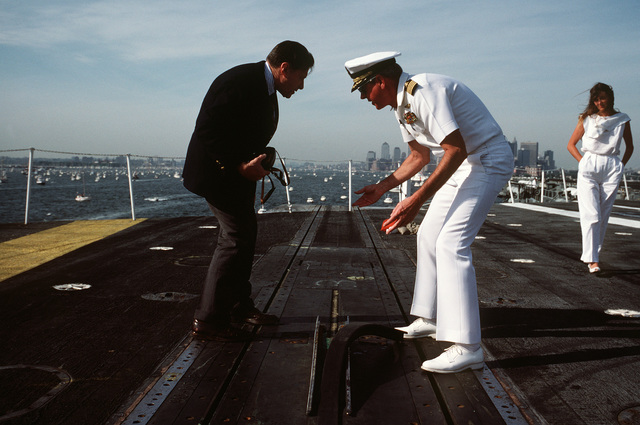 US Navy (USN) Captain (CAPT) John A. Moriarty, commanding officer of the aircraft carrier USS JOHN F. KENNEDY (CV 67), explains the flight deck catapult mechanism to Secretary of Defense Caspar W. Weinberger. Weinberger is touring the ship during the International Naval Review celebrating the centennial of the Statue of Liberty
