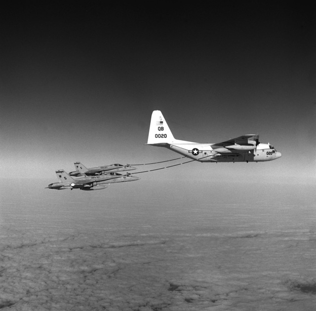 An air-to-air right side view of two Marine Fighter Attack Squadron 323 (VMFA-323) F/A-18A Hornet aircraft refueling from a Marine Aerial Refueler Transport Squadron 352 (VFGR-352) KC-130R Hercules aircraft. The aircraft are in flight over the Southern California Desert