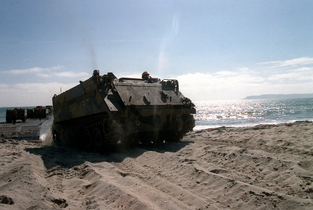 An M-113A1 armored personnel carrier is driven from a floating causeway onto a beach during exercise Gallant Eagle '86