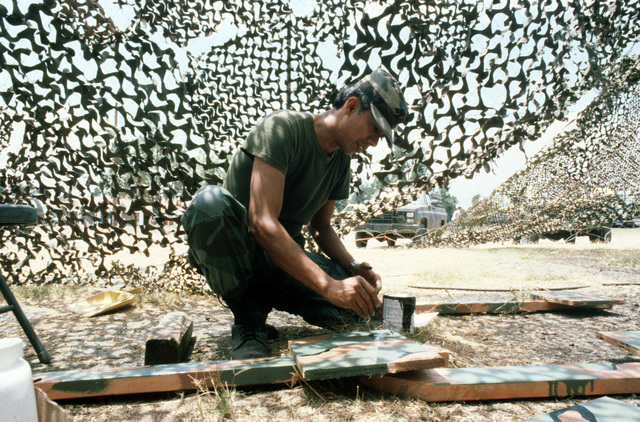 A member of the 86th Signal Battalion paints camouflage support boards during Exercise GALLANT EAGLE 86