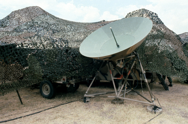A microwave dish is set up beside camouflage netting during Exercise GALLANT EAGLE 86