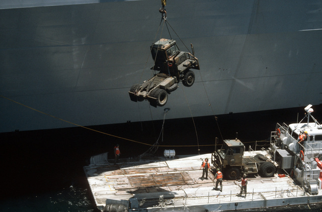 Ground support equipment is lowered onto a US Army LACV-30 (Lighter Air Cushion Vehicle - 30 Ton) hovercraft next to the vehicle cargo ship USNS ALTAIR (T-AKR 291) FOR transport to a beach during Exercise GALLANT EAGLE '86
