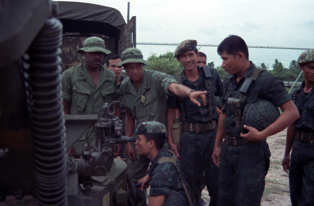 A Thai Soldier looks through the sight of an M102 105 mm Howitzer as members of Battery C, 7th Battalion, 8th Field Artillery Regiment, 25th Infantry Division (Light), look on during the joint US/Thai training Exercise COBRA GOLD '86