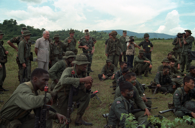 Lieutenant General (LGEN) Charles W. Bagnal, commander, US Army Western Command, center, listens to a Soldier explain jungle survival techniques at an outdoor briefing during the joint US/Thai training Exercise COBRA GOLD '86. In civilian clothing is William Brown, US ambassador to Thailand