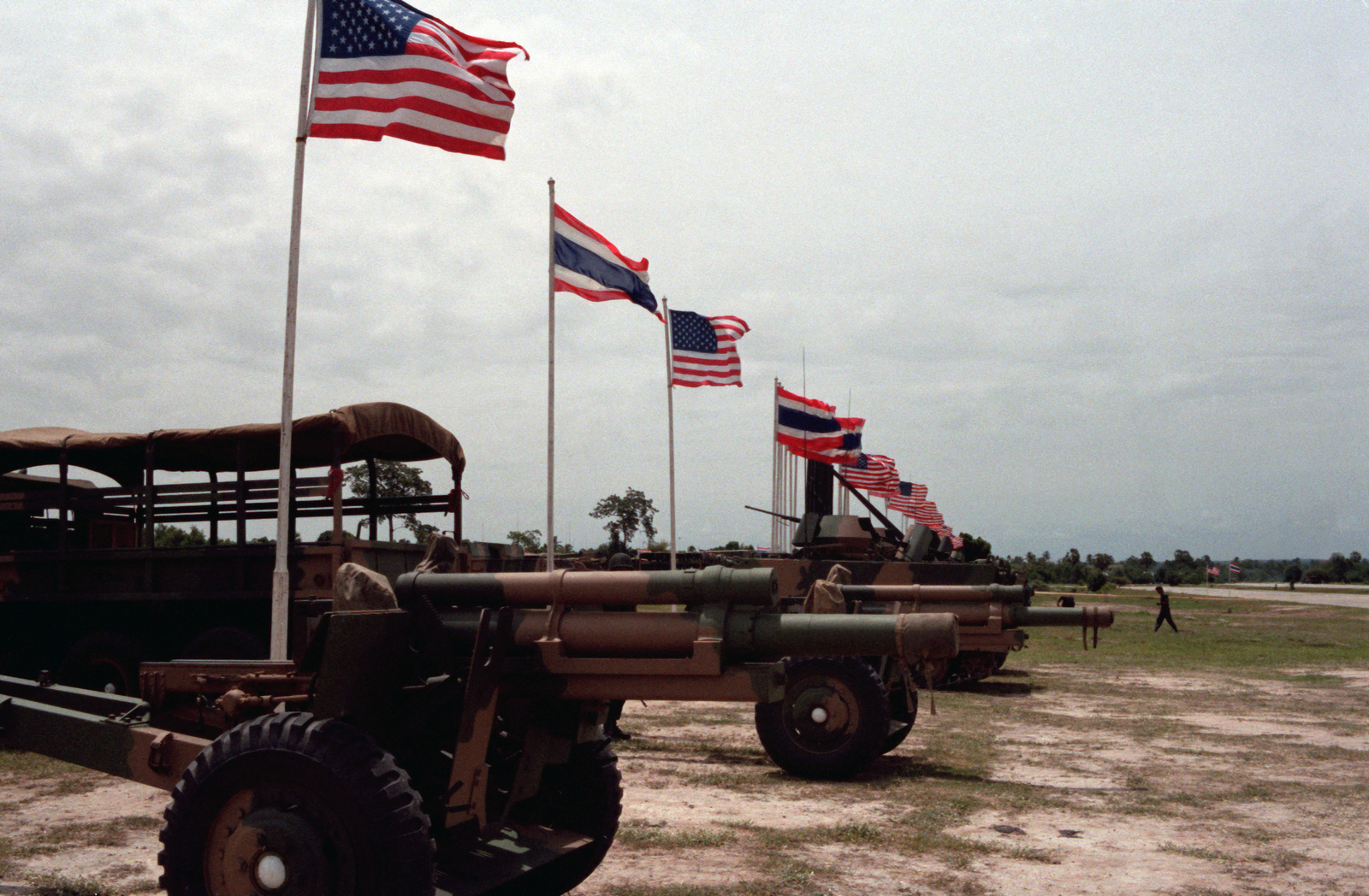 M101 105 mm Howitzers are lined up under US and Thai flags