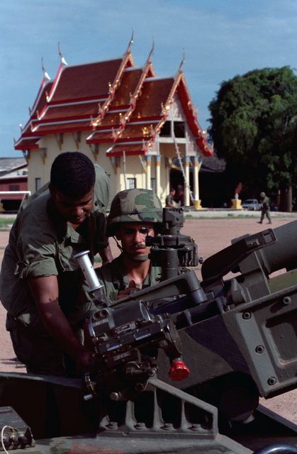 Soldiers from Battery C, 7th Battalion, 8th Field Artillery Regiment, 25th Infantry Division (Light), clean an M102 105 mm Howitzer near a Buddist temple in the Ban Khai area during the joint US/Thai training Exercise COBRA GOLD '86
