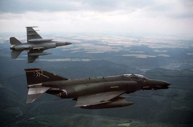 An air to air right side view of a 50th Tactical Fighter Wing F-4G Advanced Wild Weasel Phantom II aircraft, foreground, and a 50th Tactical Figher Wing F-16C Fighting Falcon aircraft banking to the left