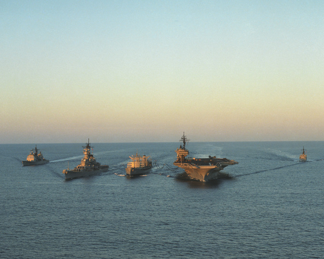 A bow view of a Military Sealift Command ship and US Navy ships underway.  They are, left to right: the guided missile cruiser USS VALLEY FORGE (CG 50), battleship USS MISSOURI (BB 63), fleet oiler USNS KAWISHIWI (T-AO 146), aircraft carrier USS KITTY HAWK (CV 63) AND the guided missile frigate USS RAMSEY (FFG 2)