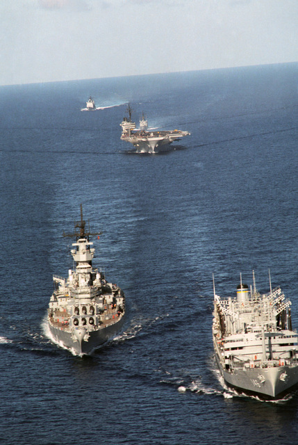 A bow view of a Military Sealift Command ship and US Navy ships underway.  They are, front to back: fleet oiler USNS KAWISHIWI (T-AO 146), battleship USS MISSOURI (BB 63), aircraft carrier USS KITTY HAWK (CV 63), guided missile frigate USS RAMSEY (FFG 2) and the guided missile cruiser USS VALLEY FORGE (CG 50)