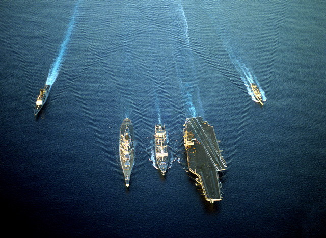 An aerial bow view of a Military Sealift Command ship and U.S. Navy ships underway. They are, left to right: the guided missile cruiser USS VALLEY FORGE (CG-50), battleship USS MISSOURI (BB-63), fleet oiler USNS KAWISHIWI (T-AO-146), aircraft carrier USS KITTY HAWK (CV-63) and the guided missile frigate USS RAMSEY (FFG-2)