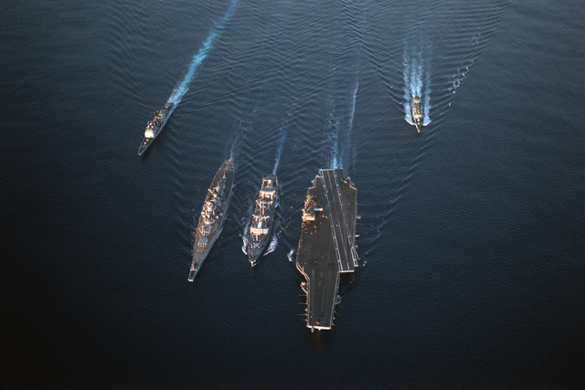 An aerial bow view of a Military Sealift Command ship and US Navy ships underway.  They are, left to right:  the guided missile cruiser USS VALLEY FORGE (CG 50), battleship USS MISSOURI (BB 63), fleet oiler USNS KAWISHIWI (T-AO 146), aircraft carrier USS KITTY HAWK (CV 63) and the guided missile frigate USS RAMSEY (FFG 2)