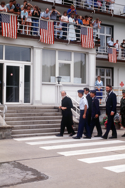 The Reverend Lawrence Jenco, a Roman Catholic priest, who was recently released after 19 months of captivity in Lebanon, enters the Weisbaden Regional Medical Center with an entourage of Air Force, Army and State Department officials