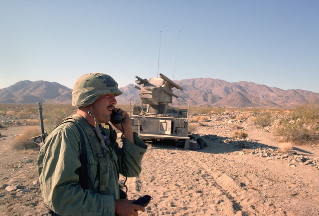 A radioman from the 4th Battalion, 1ST Air Defense Artillery, maintains radio contact with his missile battery during Exercise GALLANT EAGLE '86. An M-48A1 Chaparral low-altitude self-propelled surface-to-air missile system is in the background