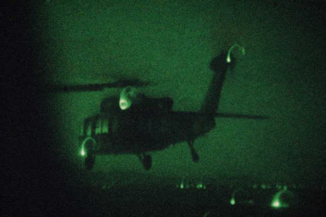 A left rear view of a US Air Force UH-60A Black Hawk (Blackhawk) helicopter from the 55th Aerospace Rescue and Recovery Squadron in flight during Exercise GALLANT EAGLE '86. (Night view shot with Nikon camera and Noctron 5 attachment)