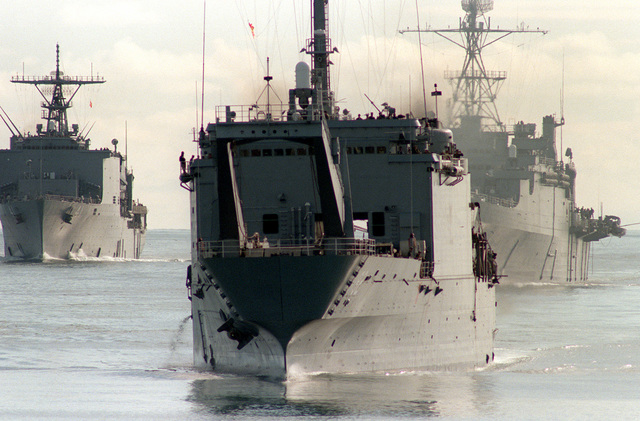 "A port bow view of the tank landing ship USS SPARTANBURG COUNTY (LST-1192), the dock landing ship USS WHIDBEY ISLAND (LSD-41), background, left, and the amphibious transport dock USS NASHVILLE (LPD-13), background, right, participating in ""leapfrog"" maneuvering drills while en route to NATO exercise Northern Wedding '86"