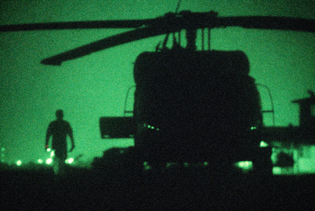 A silhouetted front view of a US Air Force UH-60A Black Hawk (Blackhawk) helicopter parked on the flight line. The 55th Aerospace Rescue and Recovery Squadron aircraft is being used during Exercise GALLANT EAGLE '86. (Night view shot with Nikon camera and Noctron 5 attachment)